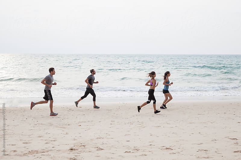 Group of friends running together at the beach by Jovo Jovanovic for Stocksy United