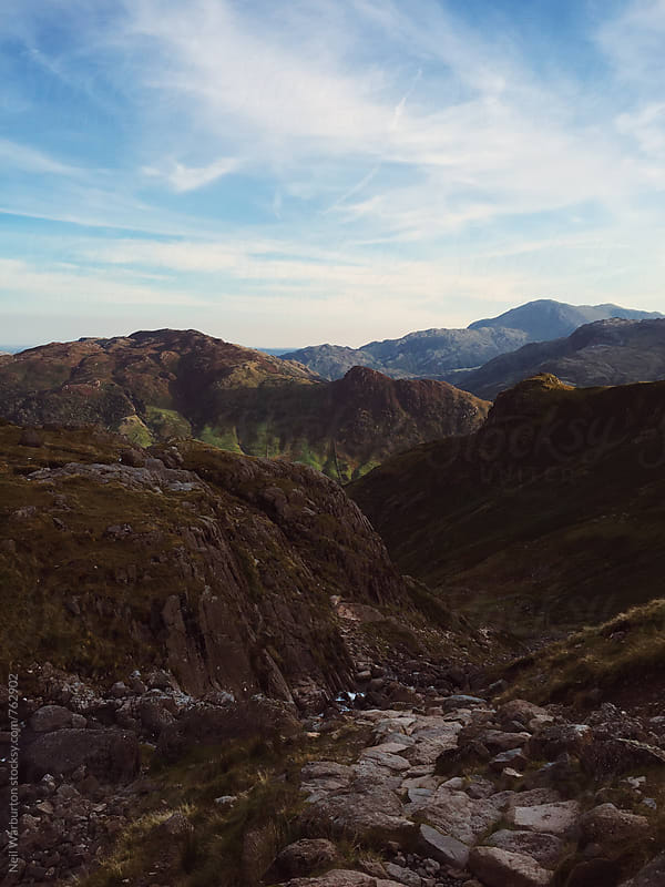 Rocky path with mountains in the distance by Neil Warburton for Stocksy United