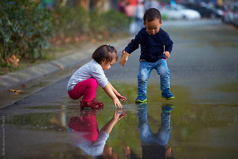 two kids playing the water in the road after rain by Bo Bo for Stocksy United