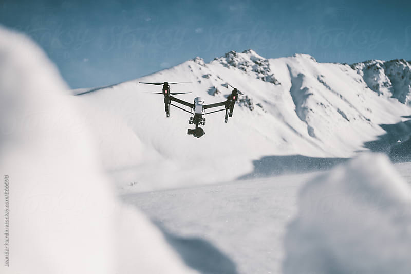 drone ready for take off in snowcovered mountain landscape by Leander Nardin for Stocksy United