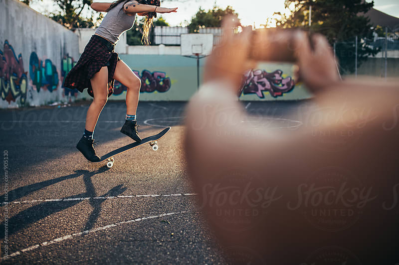 Young girl skateboarding with friend taking her photos by Jacob Lund for Stocksy United