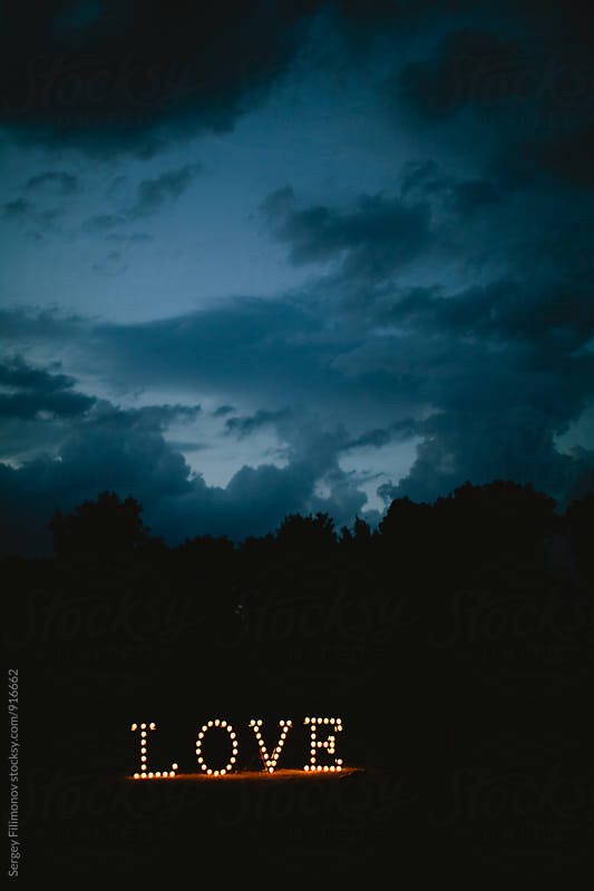Glowing light bulb with the word love in the night by Sergey Filimonov for Stocksy United