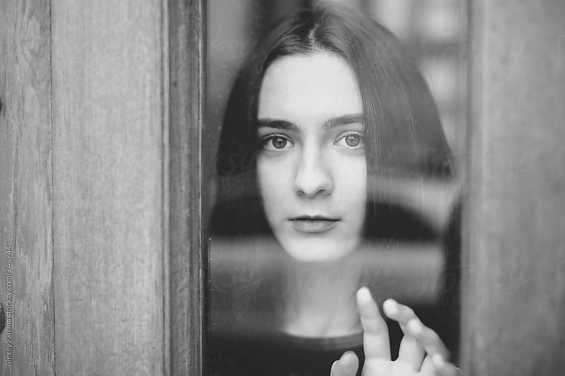 young woman standing at the window watching the street by Vesna for Stocksy United