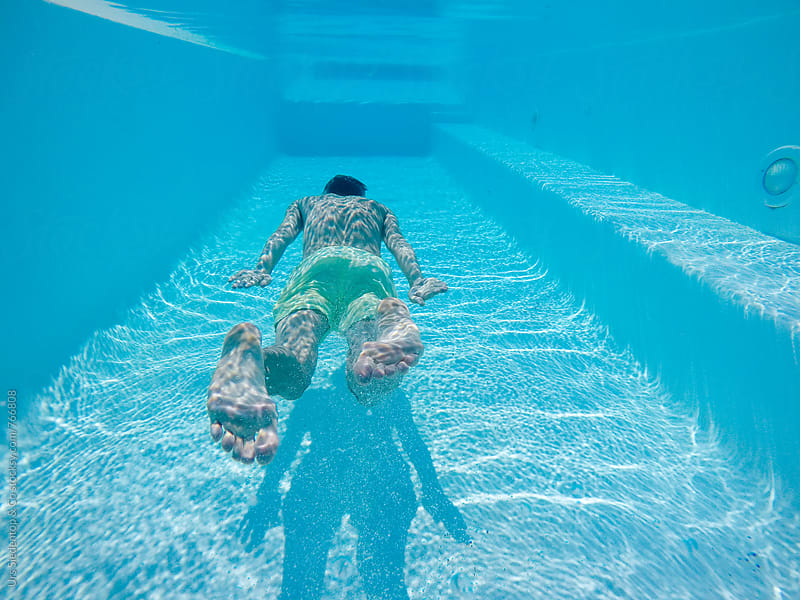 Underwater shot of man floating in swimming pool by Urs Siedentop & Co for Stocksy United