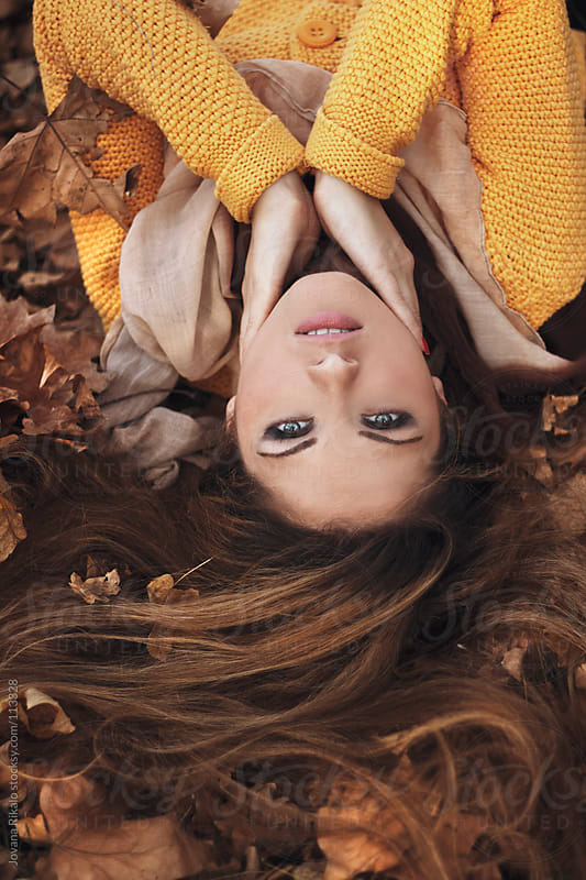 Young beautiful girl surrounded with leaves in park by Jovana Rikalo for Stocksy United