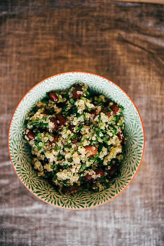 Healthy quinoa salad ; Tabbouleh salad with quinoa, tomatoes and parsley by Adrian Cotiga for Stocksy United