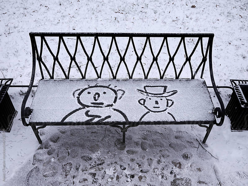 Two characters drawn on a snowy bench by Amos Chapple for Stocksy United