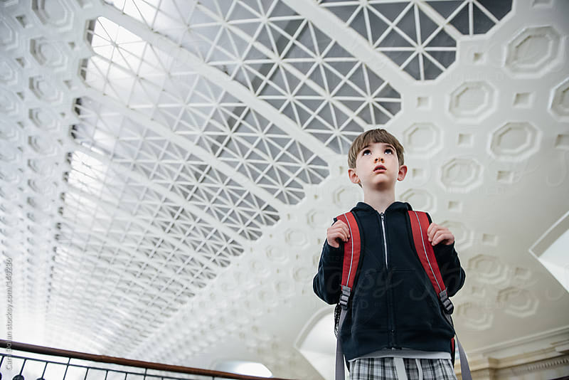 Boy with backpack stands in a station, waiting for his train by Cara Dolan for Stocksy United
