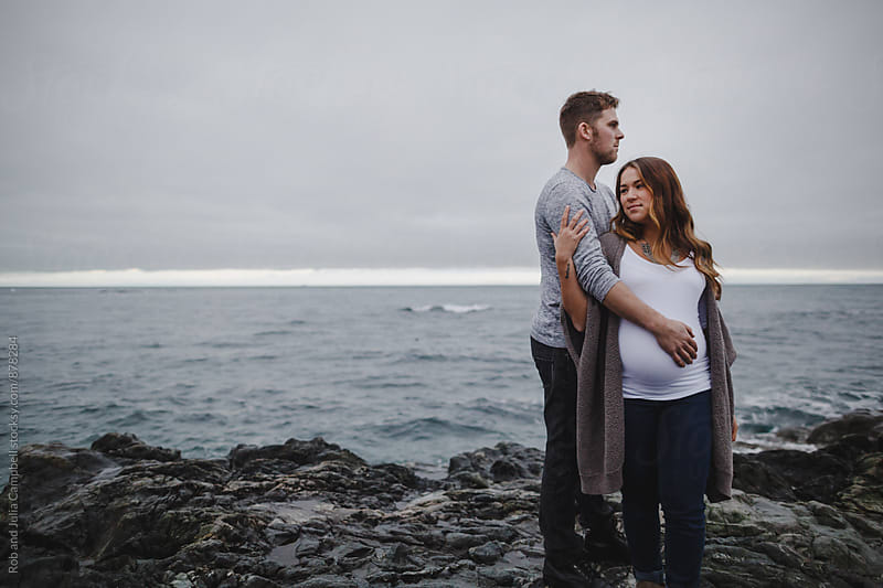 Young pregnant couple holding each other outside near ocean by Rob and Julia Campbell for Stocksy United