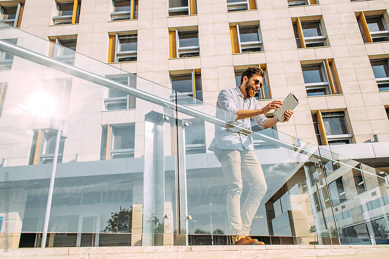 Young Caucasian businessman using a digital tablet in front of a corporate building. by Studio Firma for Stocksy United