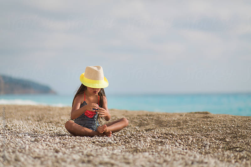 Girl with yellow hat sitting on a beach. by Dejan Ristovski for Stocksy United