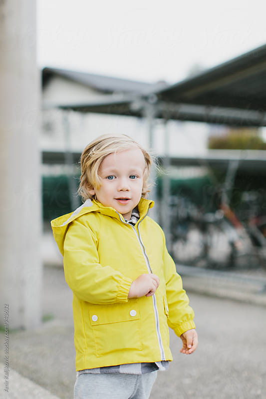 Cute attractive little boy in a yellow jacket by Amir Kaljikovic for Stocksy United