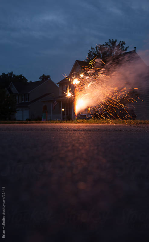 Fireworks sparking on road though American Neighborhood, July 4th by Brian McEntire for Stocksy United