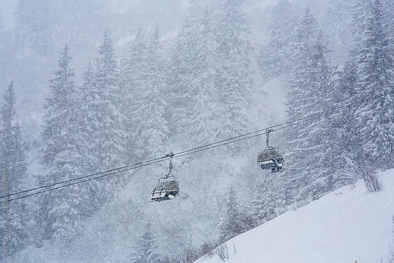 Chair lifts moving skiers up at a ski area in the mountains in winter during a snowfall by Soren Egeberg for Stocksy United