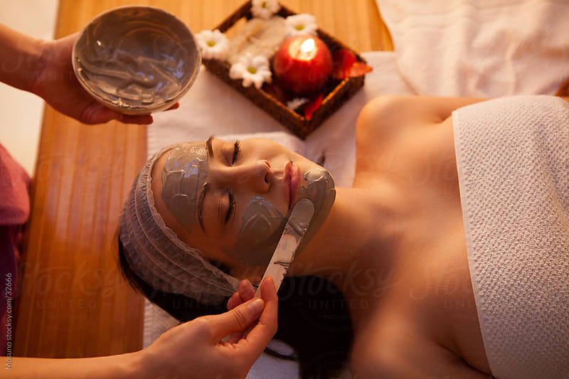 Woman applying facial mask on a client's face in a spa center. by Mosuno for Stocksy United