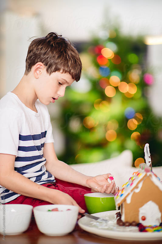 Boy decorating a gingerbread house by Angela Lumsden for Stocksy United