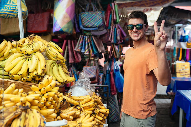 Young man with sunglasses at a local market in Mexico next to a stack of yellow bananas and a handbag bazaar by Alejandro Moreno de Carlos for Stocksy United
