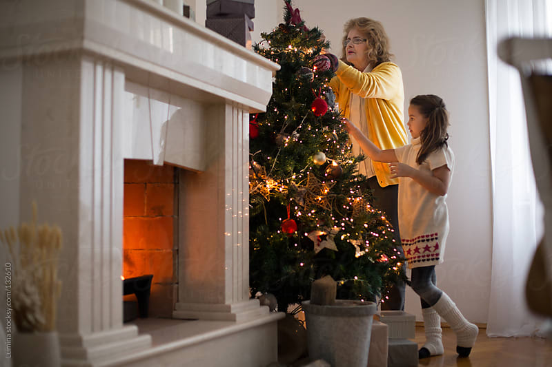 Grandma and Granddaughter Decorating the Christmas Tree by Lumina for Stocksy United