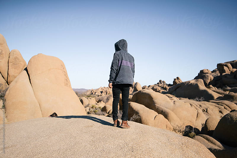 Man in jacket looking out over Joshua Tree, California by Jeremy Pawlowski for Stocksy United