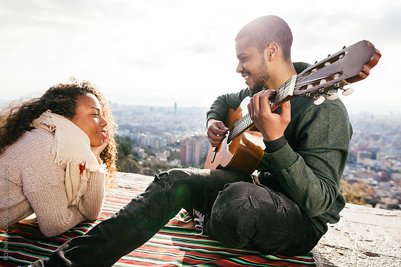 Latin man playing guitar with his girlfriend above city. by BONNINSTUDIO for Stocksy United