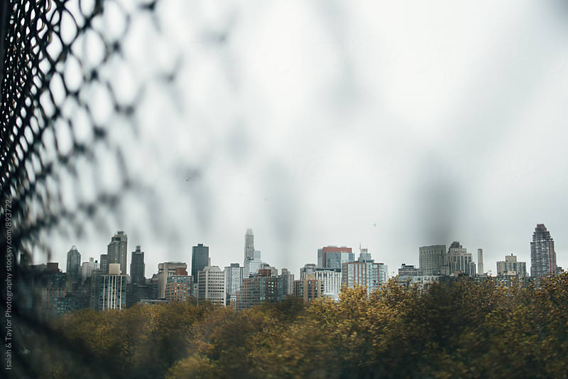 City Through Fence by Isaiah & Taylor Photography for Stocksy United