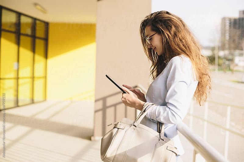 Beautiful businesswoman using her tablet by Aleksandar Novoselski for Stocksy United