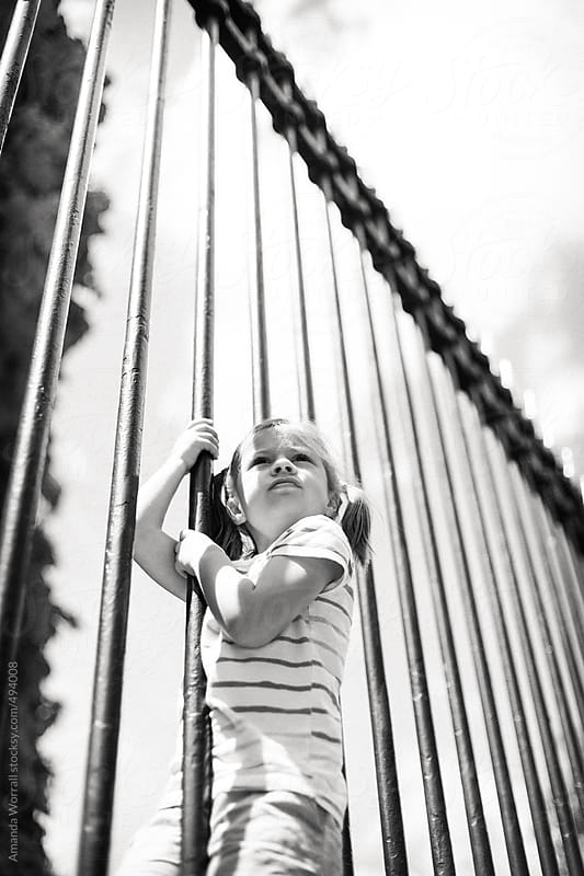 Young girl climbing on tall iron fence by Amanda Worrall for Stocksy United