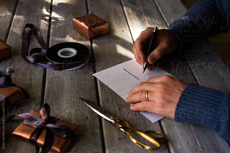 Man writing a Christmas card by Helen Rushbrook for Stocksy United