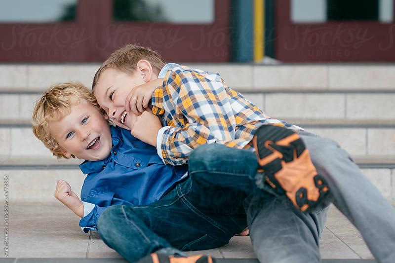 Two boys playing on the front steps of a school by Ania Boniecka for Stocksy United