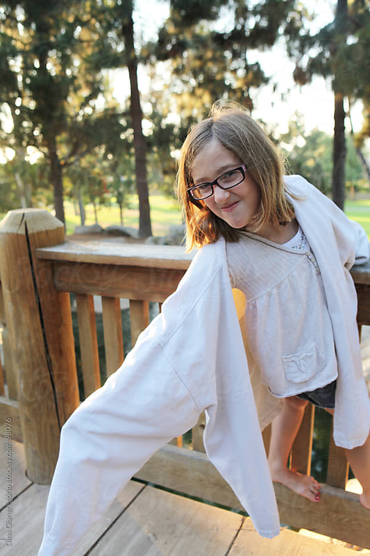 Young girl in oversized jacket holding on wood railing by Dina Giangregorio for Stocksy United