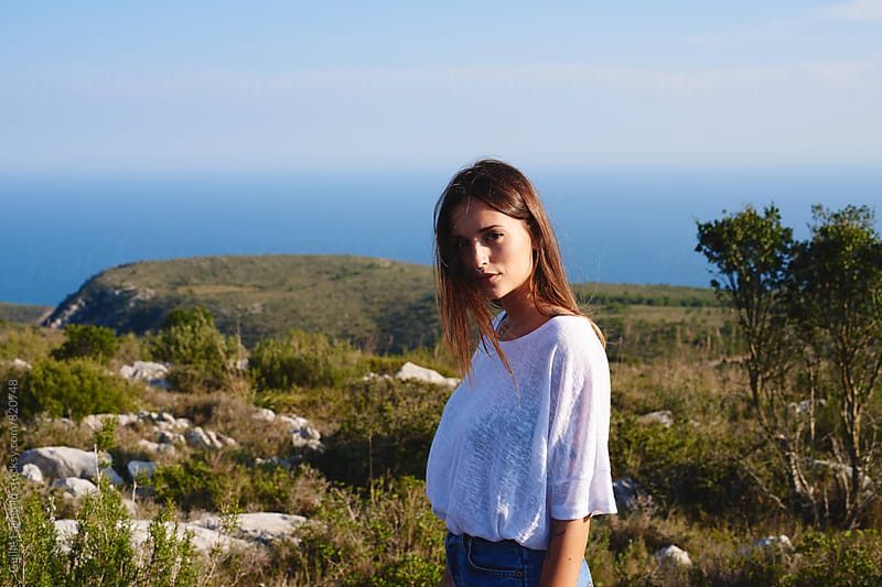 Young woman standing against of beautiful seascape by Guille Faingold for Stocksy United