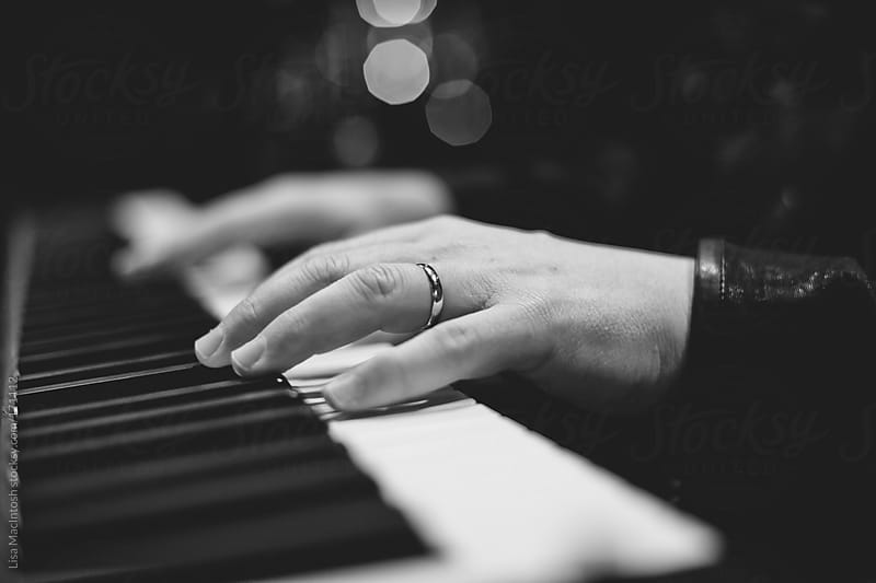 mans hands with wedding ring playing piano by Lisa MacIntosh for Stocksy United