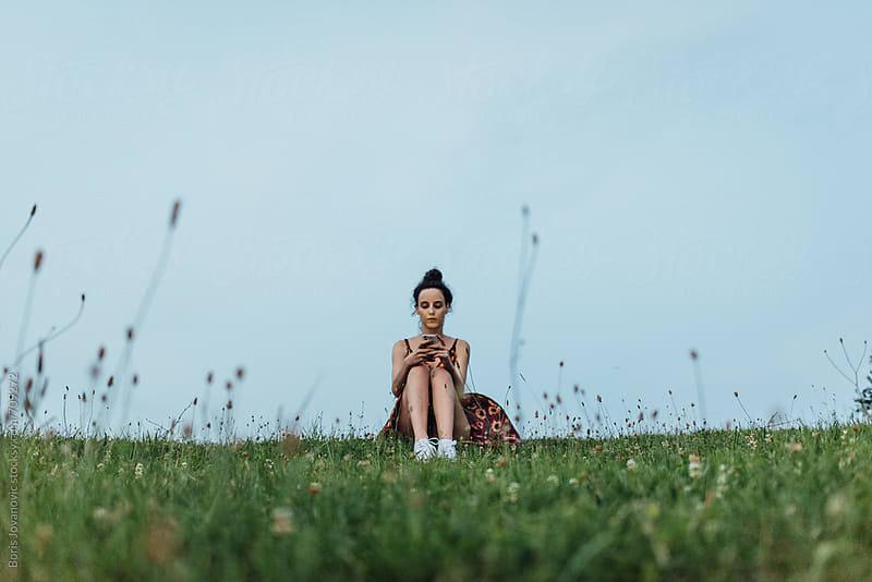 Woman sitting in grass by Boris Jovanovic for Stocksy United