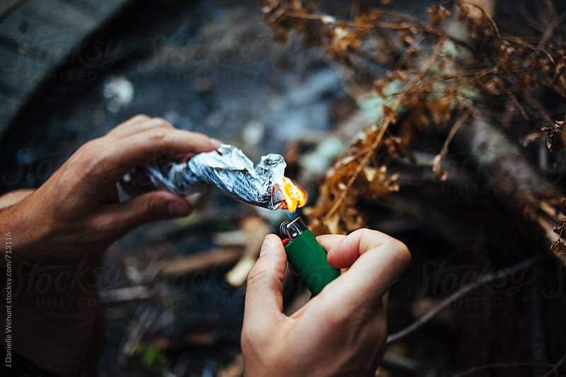 A pair of caucasian man hands lighting paper for a campfire. by J Danielle Wehunt for Stocksy United