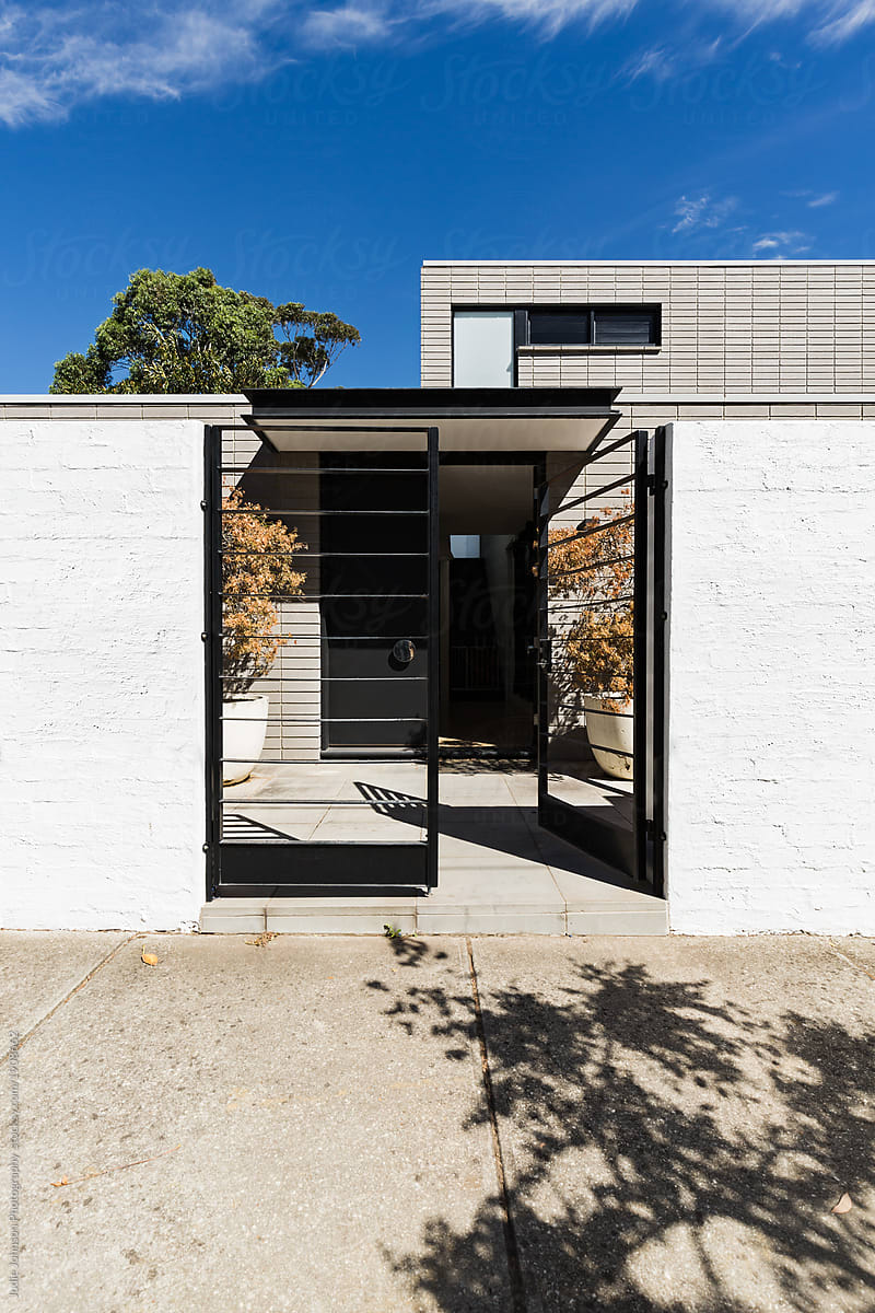 Contemporary architectural home facade with welcoming open gate by Jodie  Johnson - Architecture, House - Stocksy United