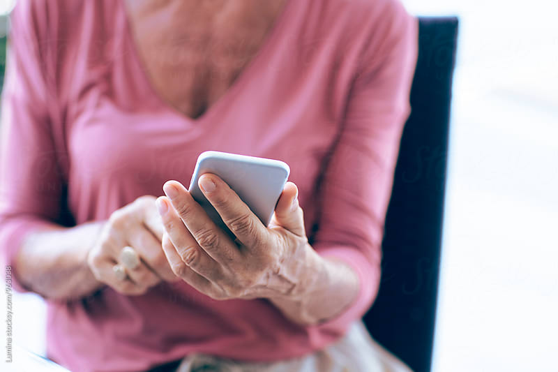 Senior Woman Sitting at Home and Texting by Lumina for Stocksy United