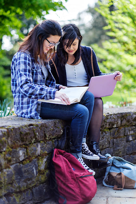 Two Asian female college students studying on campus by Suprijono Suharjoto for Stocksy United