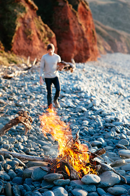 Fire on the beach with a man collecting firewood by Suzi Marshall for Stocksy United