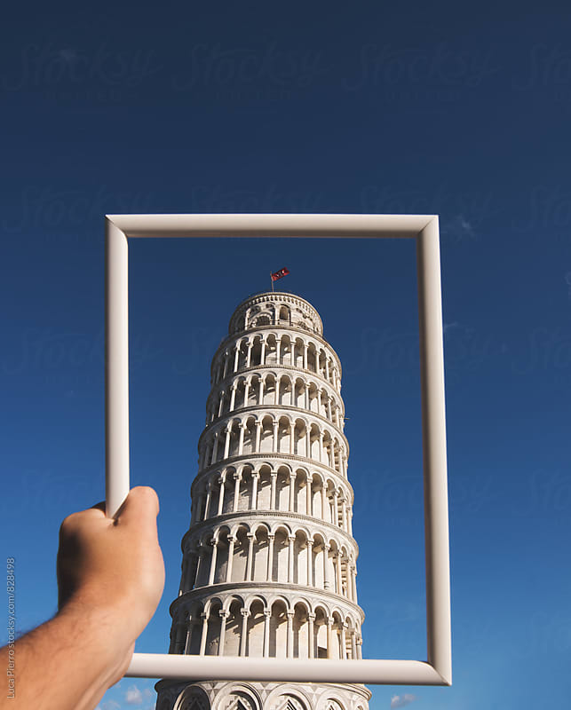 Closeup of man's hands framing the Leaning Tower of Pisa in Tuscany by Luca Pierro for Stocksy United