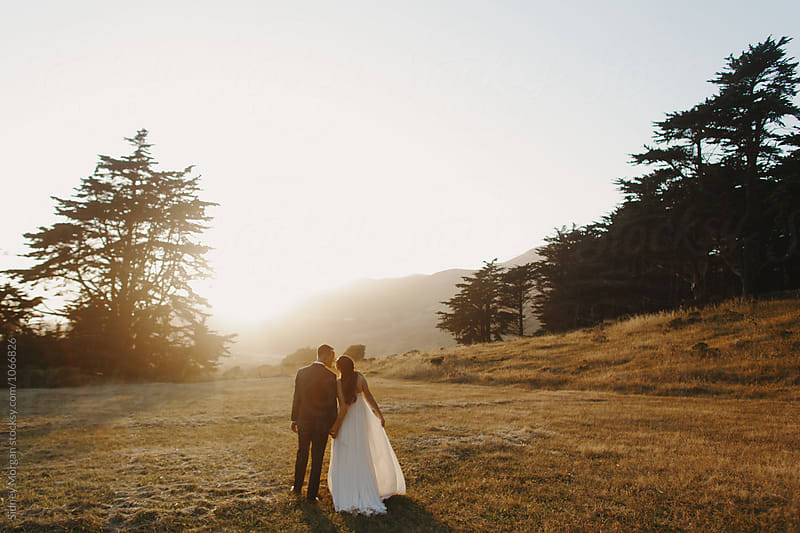 Bride and Groom Walking Toward Sunset by Sidney Morgan for Stocksy United