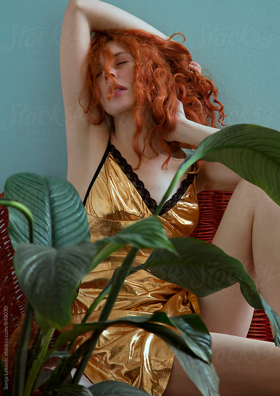 sensual redhead in a golden dress by Sonja Lekovic for Stocksy United