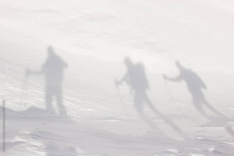 Shadows of three hikers in the snow by michela ravasio for Stocksy United