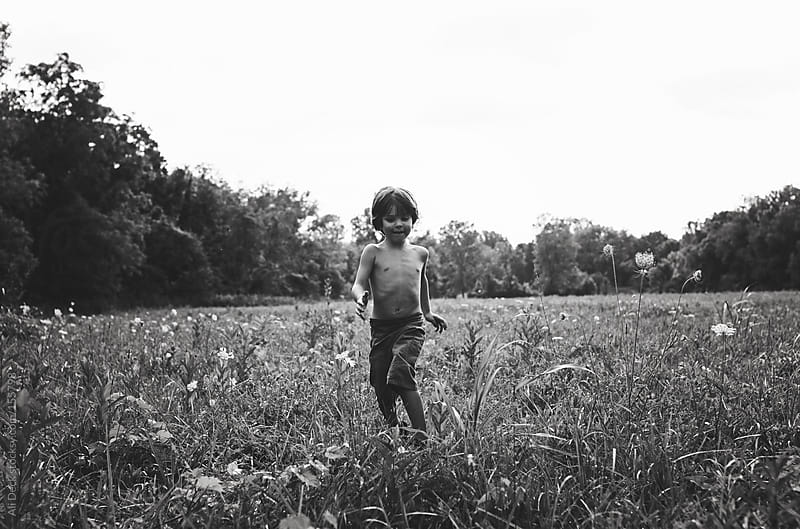 Boy Running in a Field by Ali Deck for Stocksy United