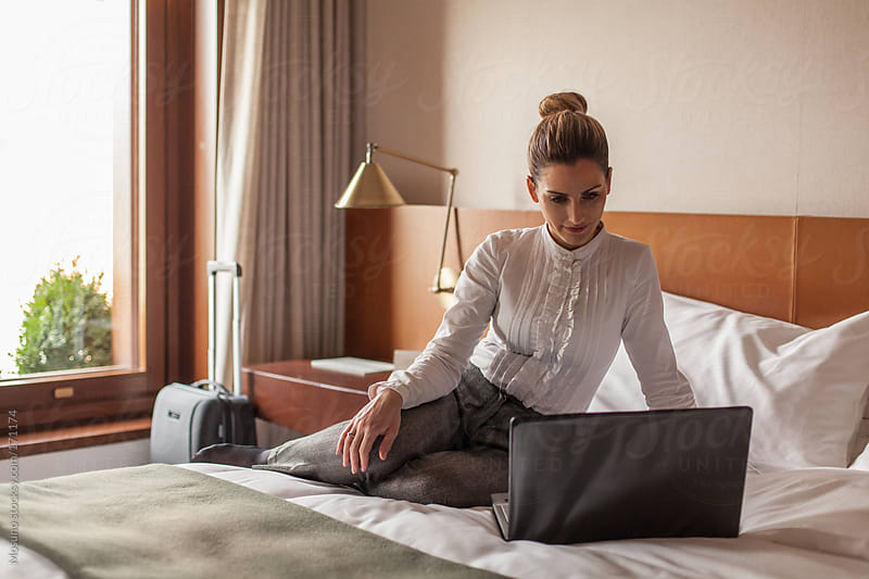 Businesswoman Using Laptop in a Hotel Room by Mosuno for Stocksy United