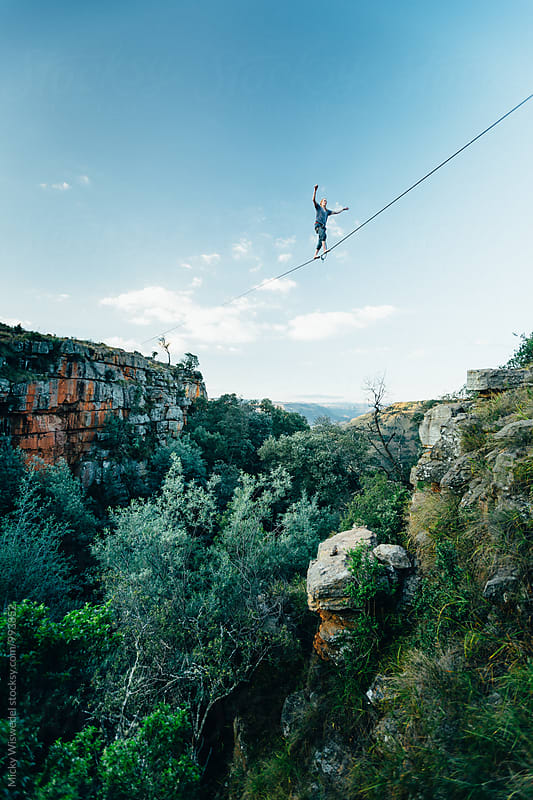 Man tightrope walking a high line over a lush gorge in the mountains by Micky Wiswedel for Stocksy United