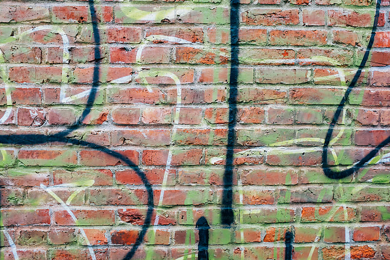 Graffiti markings on old brick wall by Paul Edmondson for Stocksy United
