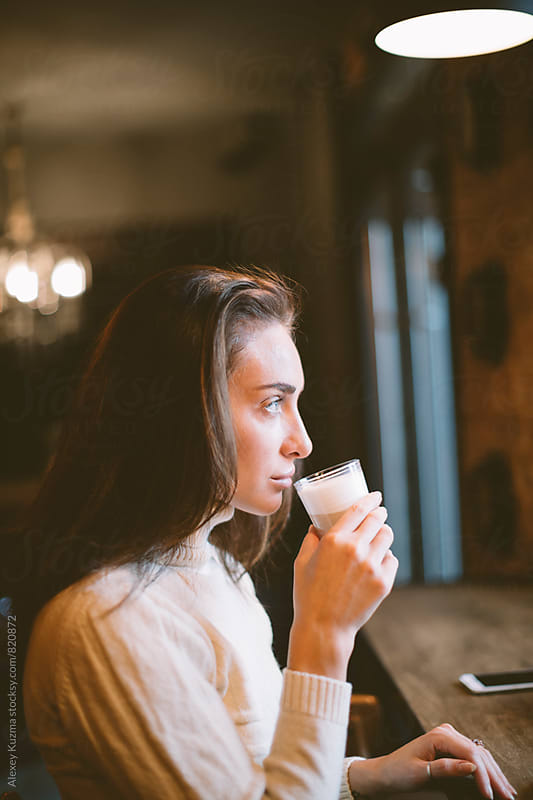 portrait of real  woman sitting in a Coffee Shop.  by Alexey Kuzma for Stocksy United