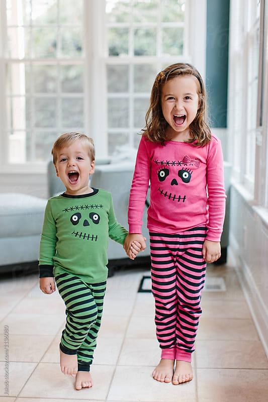 Cute siblings playing in their halloween pajamases
