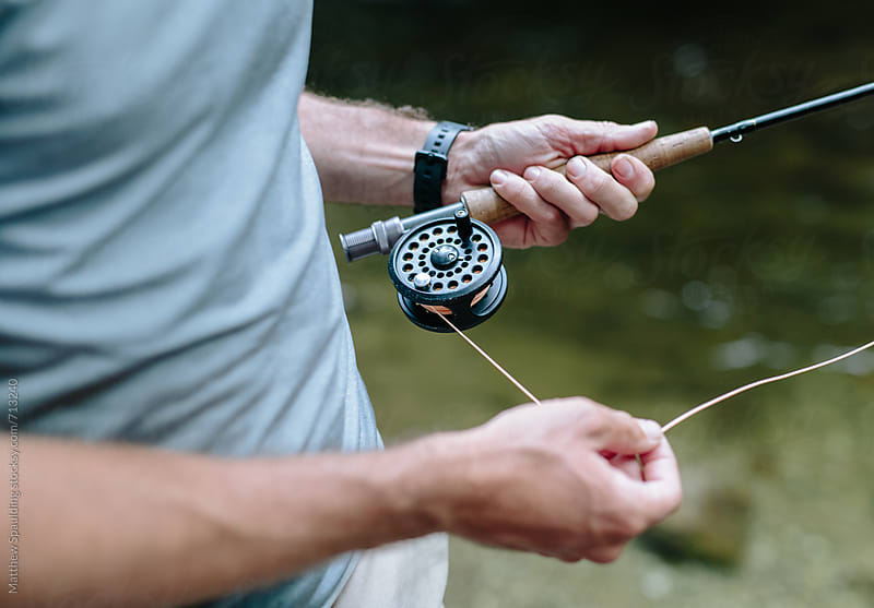 Close up of hands with fishing rod and line outdoors by Matthew Spaulding for Stocksy United