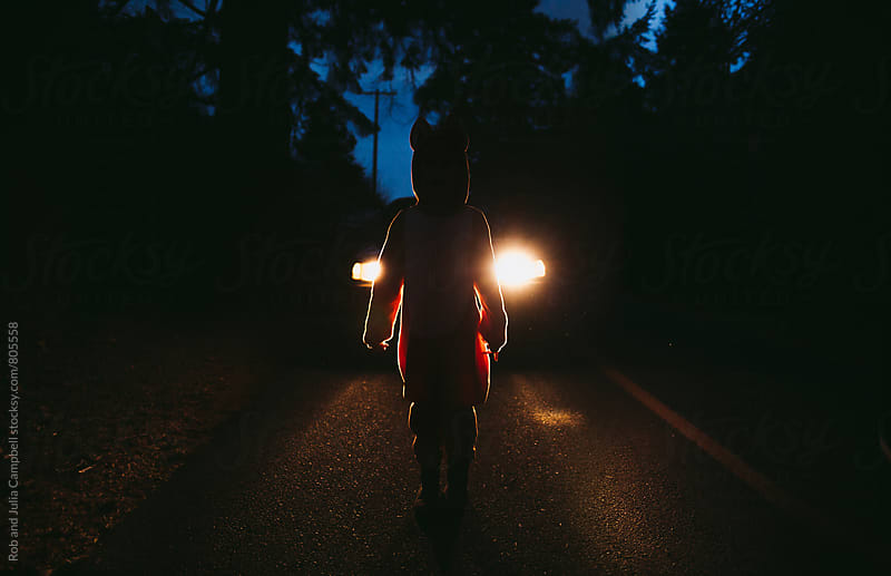 Child in fox costume standing in front of car headlights by Rob and Julia Campbell for Stocksy United